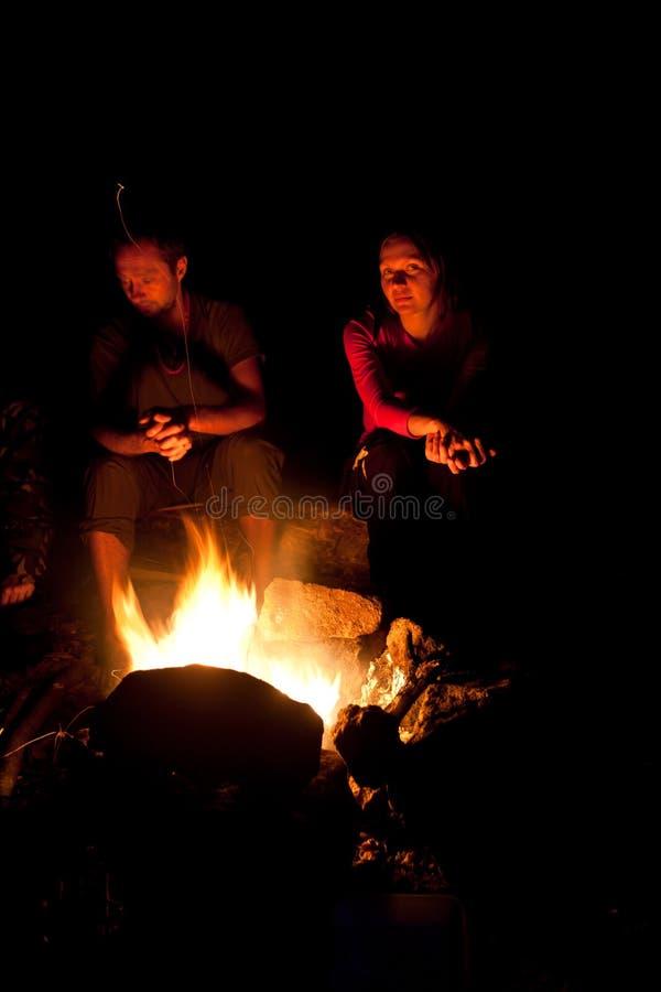 La gente si avvicina al fuoco di accampamento in foresta fotografie stock