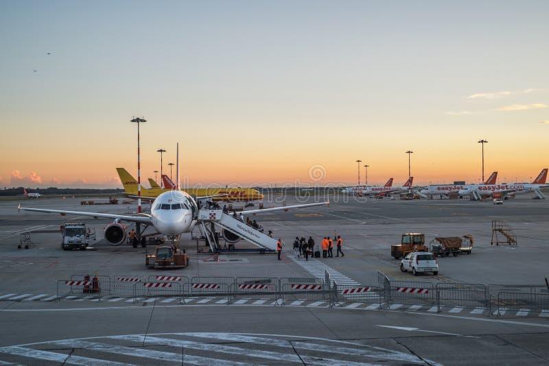 La gente si imbarca su un aeroplano commerciale all'aeroporto di Milan Malpensa al tramonto a Milano immagine stock