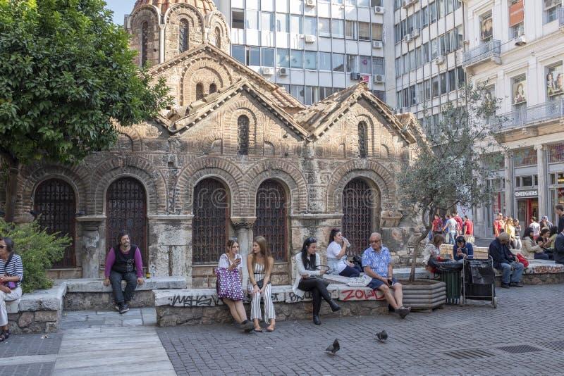 La gente si rilassa accanto alla chiesa antica ed alle costruzioni moderne a Atene immagine stock libera da diritti