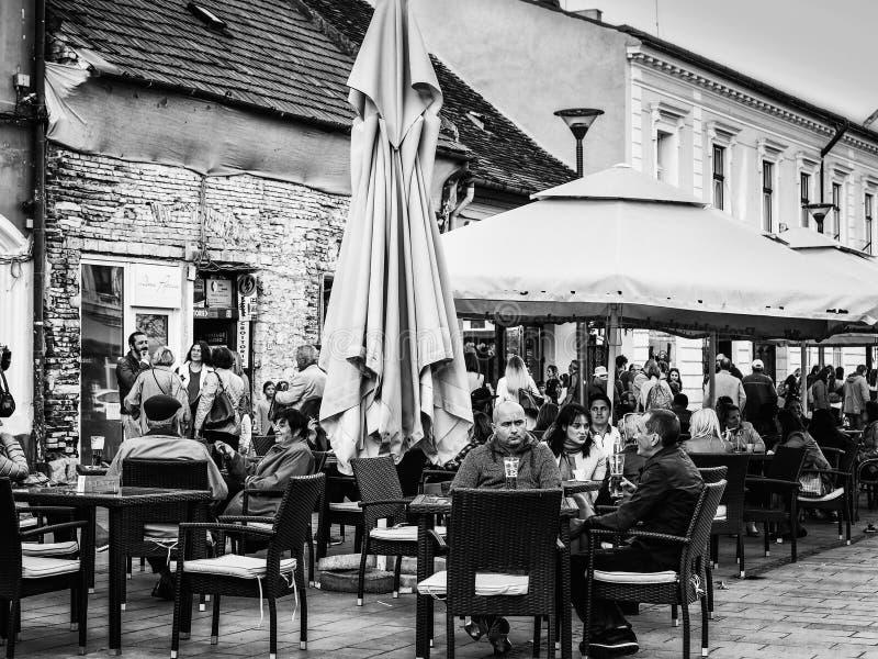 La gente si siede alle tavole e beve ad un terrazzo all'aperto fotografie stock