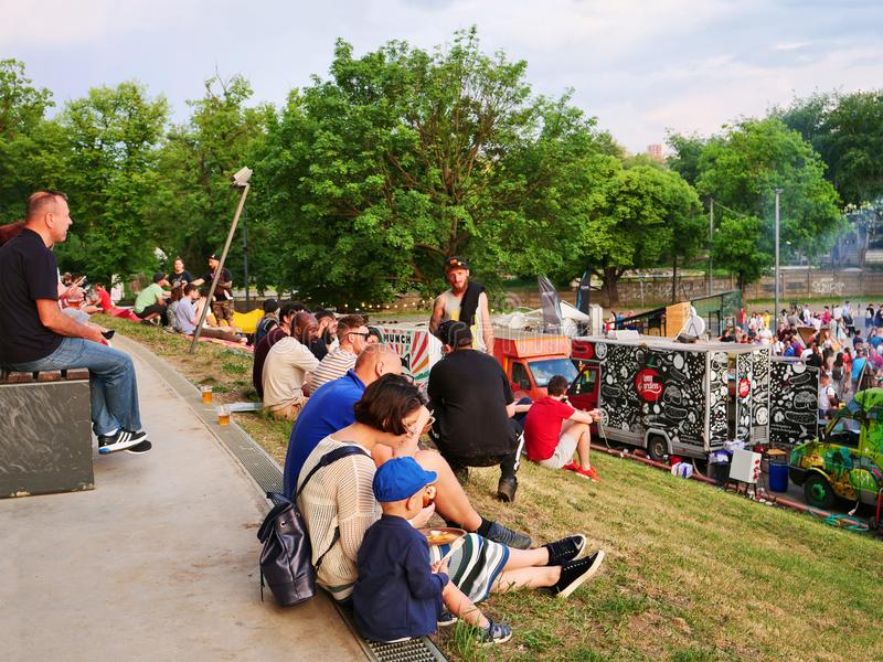 La gente si siede sull'erba ed ha uno spuntino immagine stock libera da diritti