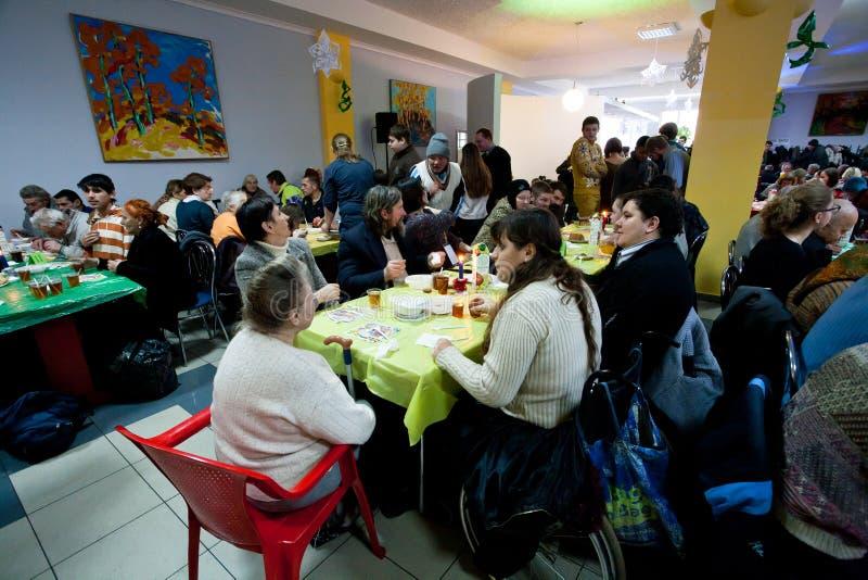La gente sin hogar y malsana se sienta alrededor de las tablas con la comida en la cena de la caridad de la Navidad para los desam fotos de archivo