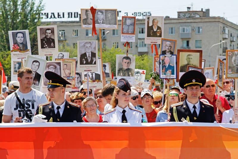 La gente sostiene la bandera del regimiento y de los retratos inmortales de sus parientes el día de la victoria en Stalingrad imagen de archivo