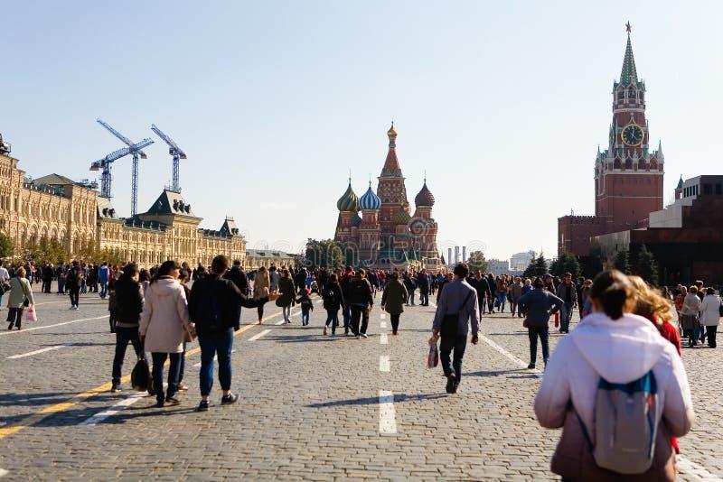La gente sta camminando lungo il quadrato rosso fotografie stock