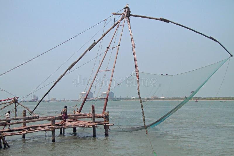 La gente sta camminando vicino alle reti da pesca cinesi nel Kochi fotografia stock