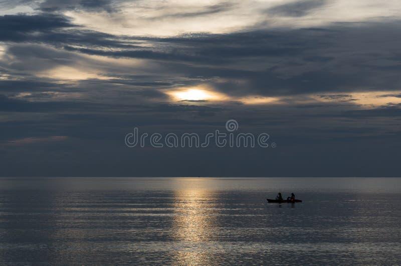 La gente sta prendendo una piccola barca del kajak mentre il sole sta mettendo immagini stock