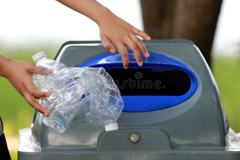 La gente sta raccogliendo le bottiglie di plastica per riciclare immagine stock