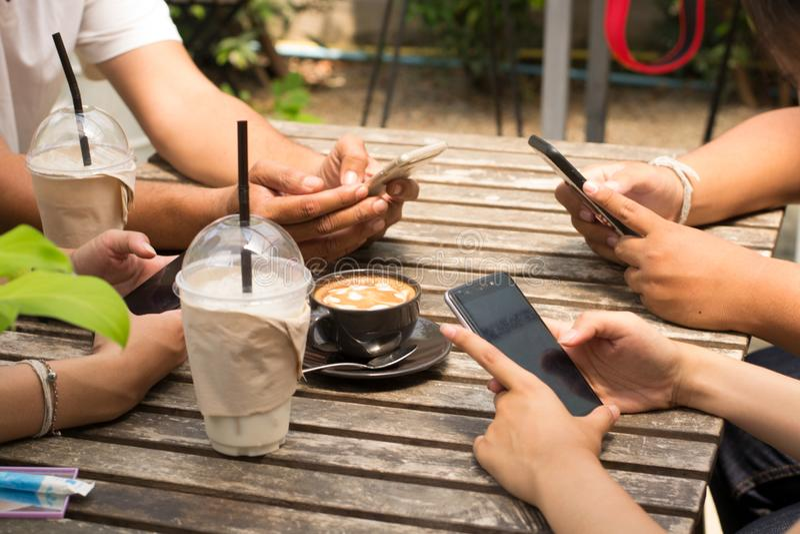 La gente sta sedendo sul telefono e sul caffè bevente su una tavola di legno in un ristorante fotografia stock libera da diritti