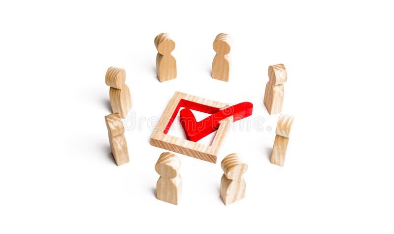 La gente sta in un cerchio ed in uno sguardo al segno di spunta nella scatola elezione, scrutinio o referendum La gente di scruti immagine stock libera da diritti