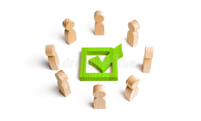 La gente sta in un cerchio ed in uno sguardo al segno di spunta verde nella scatola elezione, scrutinio o referendum La gente di  immagine stock
