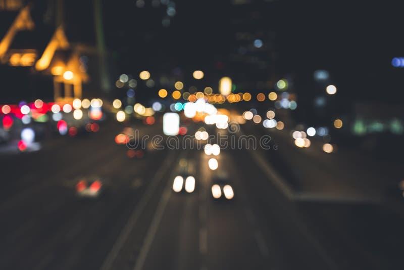 La gente sta viaggiando con le automobili alla notte nella città fotografia stock