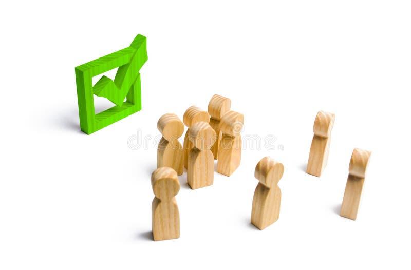 La gente sta vicino ed esamina il segno di spunta verde nella scatola elezione, scrutinio o referendum Gli elettori partecipano a fotografia stock
