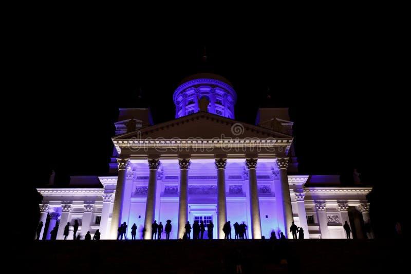 La gente stant davanti ad Helsinki illuminata San Nicola cathed immagini stock libere da diritti