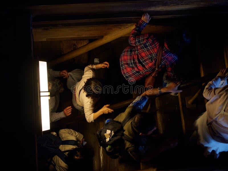 La gente sube las escaleras de madera oscuros del castillo de Himeji, Himeji, Japón imagen de archivo libre de regalías