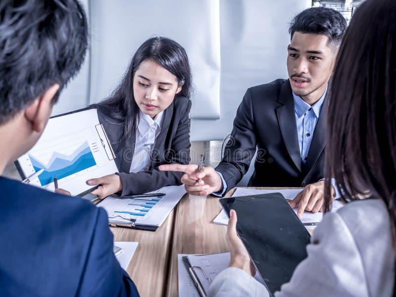 La gente sul lavoro: gruppo di affari che ha una riunione con l'ufficio del flipchart di addestramento del gruppo immagine stock