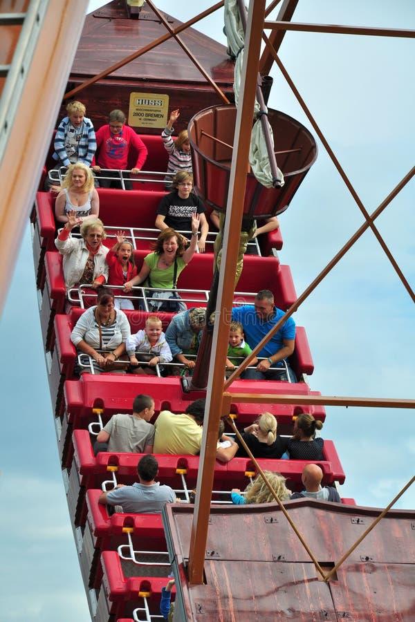 La gente sulla nave d'oscillazione sotto il cielo nuvoloso blu fotografia stock libera da diritti
