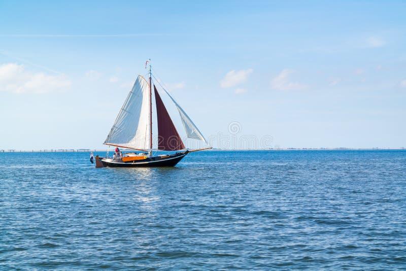 La gente sulla navigazione flatbottom della barca a vela su Waddensea vicino all'isola T fotografia stock