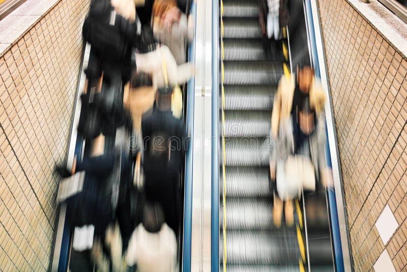 La gente sulle scale mobili nella stazione della metropolitana immagini stock libere da diritti