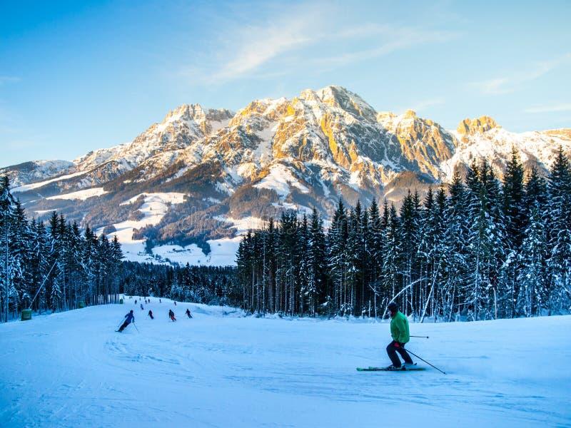 La gente sullo sci pende nella località di soggiorno di montagna sulla mattina soleggiata dell'inverno fotografie stock libere da diritti