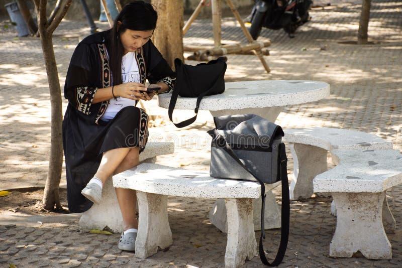 La gente tailandesa descansa y teléfono móvil del juego que se sienta en la silla de piedra en al aire libre en jardín en el temp fotografía de archivo libre de regalías