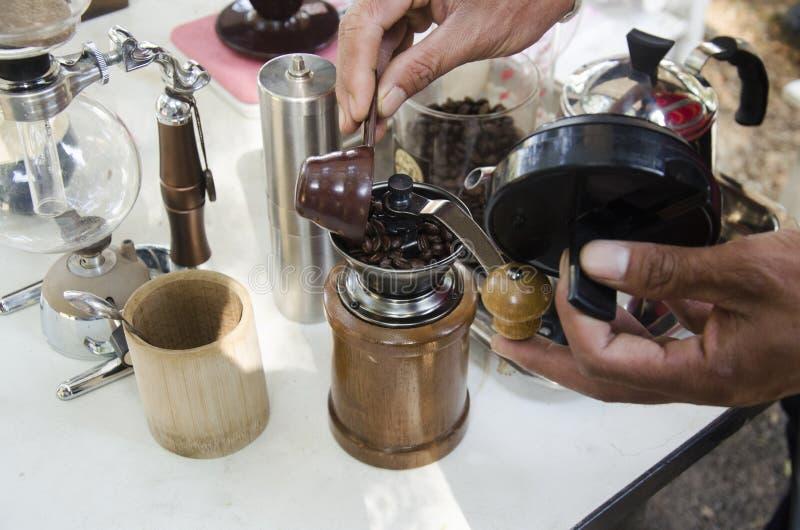 La gente tailandesa utiliza las amoladoras de café manuales antiguas hechas café para s foto de archivo