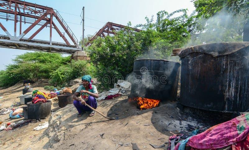 La gente teñe la ropa tradicional en riverbank imagen de archivo
