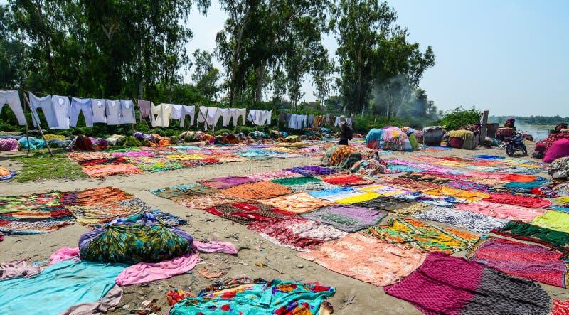 La gente teñe la ropa tradicional en riverbank imágenes de archivo libres de regalías