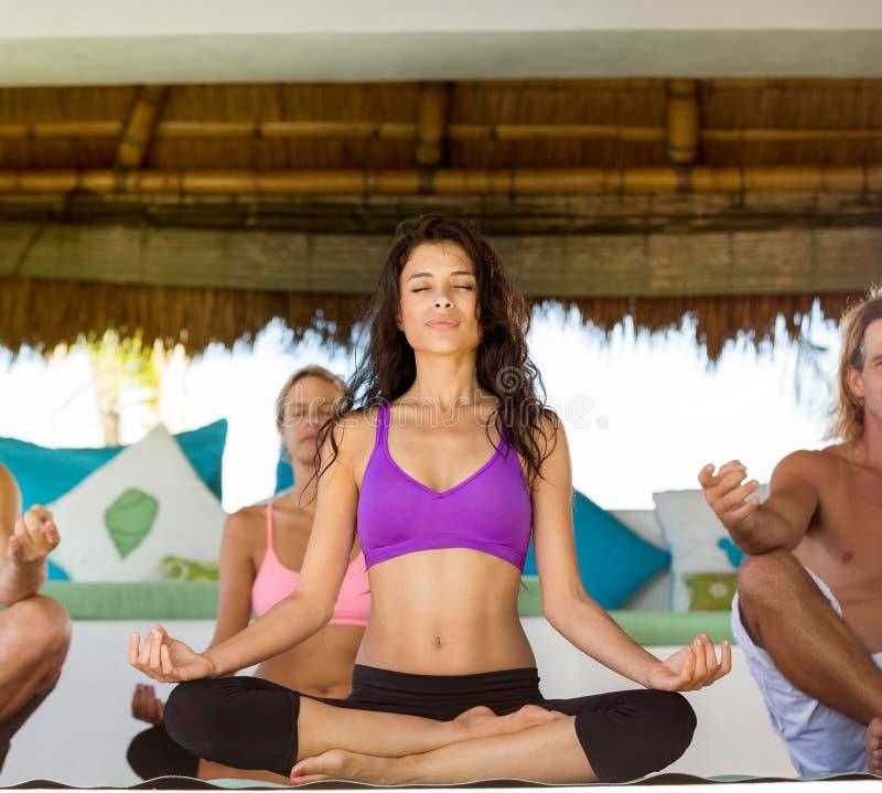 La gente tiene meditación en clase de la yoga imagen de archivo