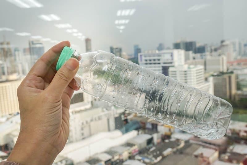La gente tiene una bottiglia di plastica trasparente per ricicla e riutilizza immagine stock libera da diritti