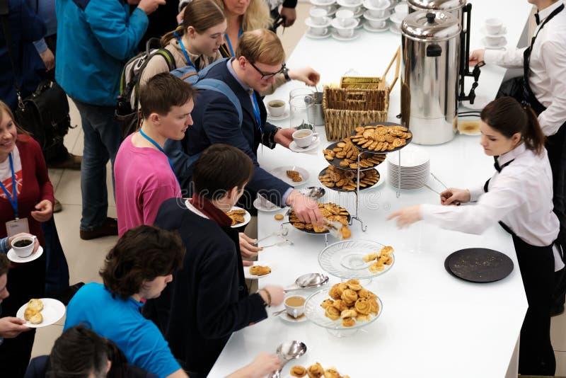 La gente toma los bollos con las pasas en un descanso para tomar café en una conferencia imágenes de archivo libres de regalías