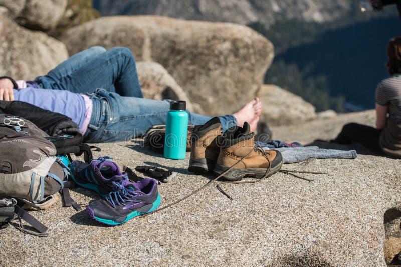 La gente turística que descansa en campo y seca los zapatos después de la montaña que camina en el parque nacional de yosemite fotografía de archivo libre de regalías