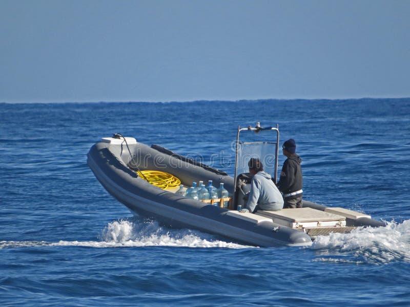 La gente in un crogiolo di battello pneumatico Due uomini nel mare fotografia stock