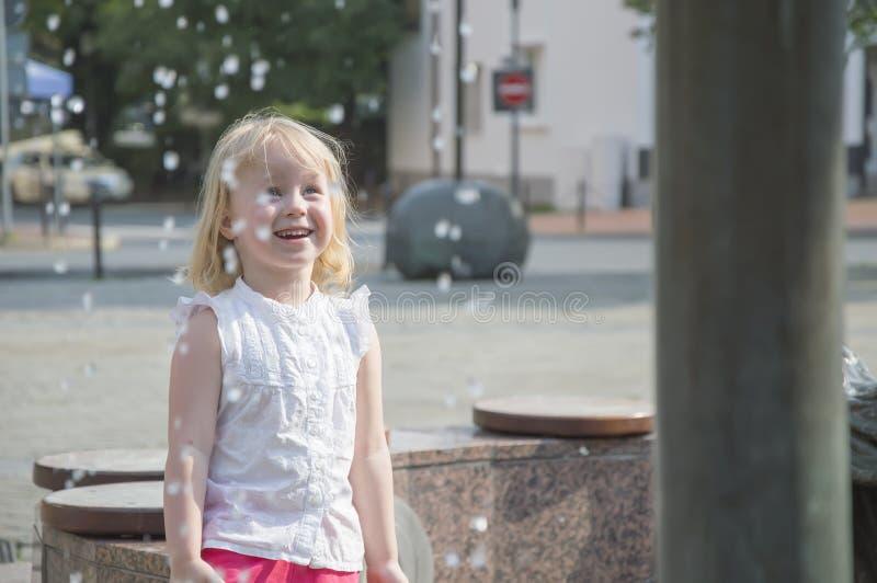 La gente, una niña juega feliz en la fuente en la estación caliente del verano imagen de archivo