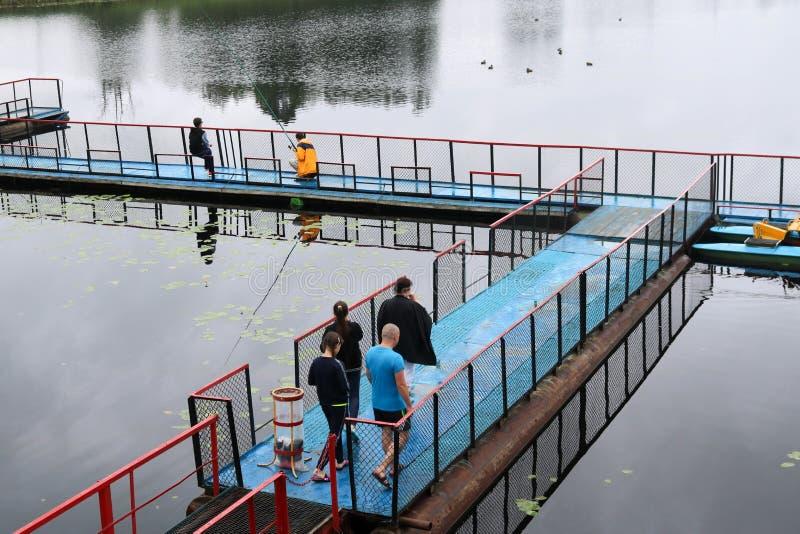 La gente, uomini sta pescando dal pontone, grembiule, ponte sul lago con le anatre al centro ricreativo, sanatori nella caduta fotografia stock libera da diritti