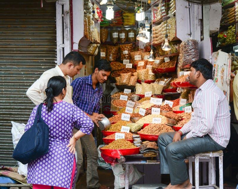 La gente vende le spezie al mercato a Delhi, India fotografia stock
