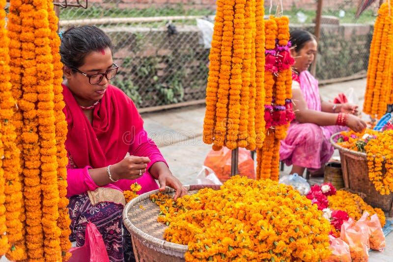 La gente vende los collares de la flor cerca al cuadrado de Katmandu Durbar imagen de archivo libre de regalías