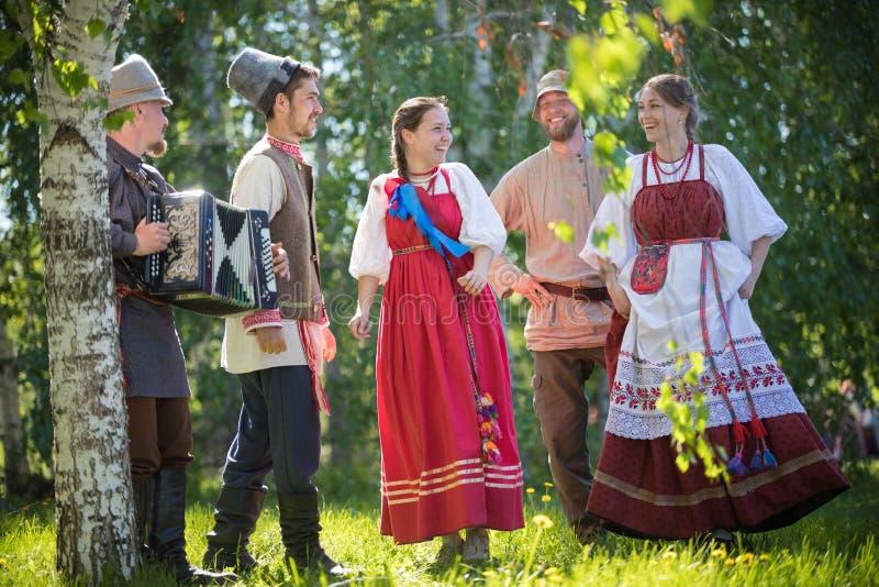 La gente in vestiti russi tradizionali sta ballando nel campo e sta parlando - uno di loro gioca la musica della fisarmonica immagine stock