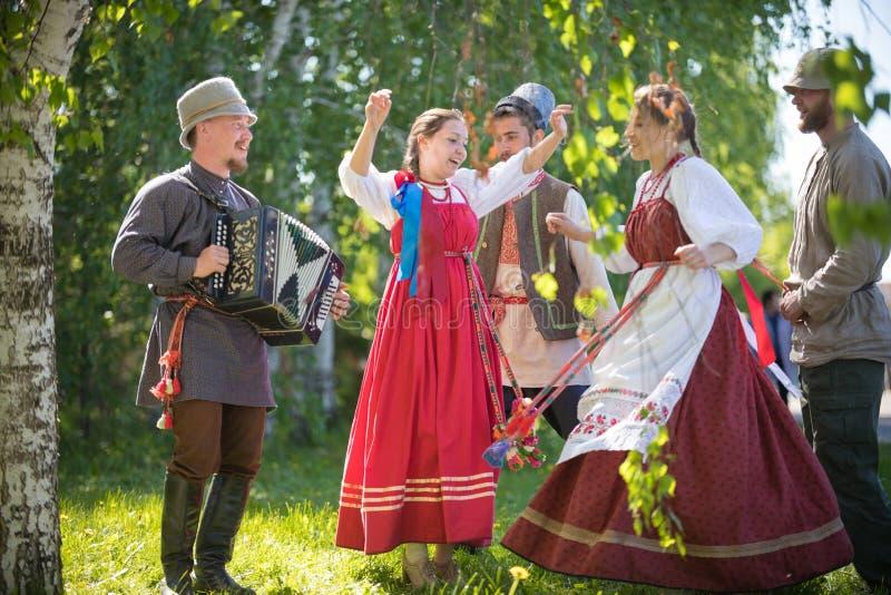 La gente in vestiti russi tradizionali sta ballando nel legno - uno di loro gioca la fisarmonica ed il canto fotografia stock