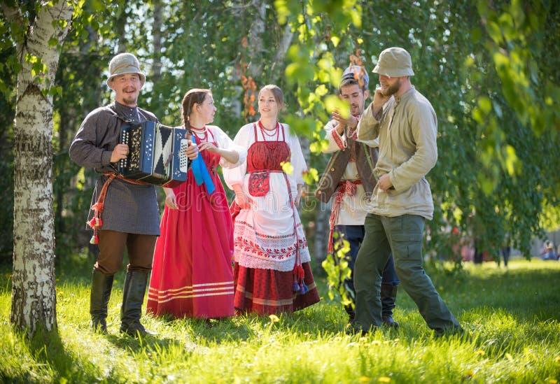 La gente in vestiti russi tradizionali sta stando nel legno e sta parlando - uno di loro gioca la fisarmonica e fotografia stock libera da diritti