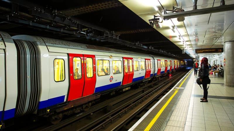 La gente viaja a través de red subterráneo del tren en Londres foto de archivo