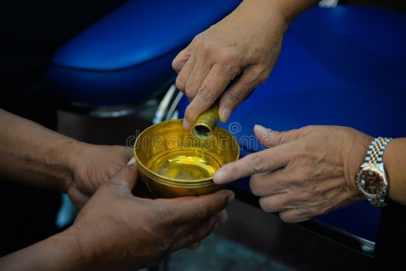 La gente vierte el agua ceremonial y ruega para el difunto foto de archivo libre de regalías