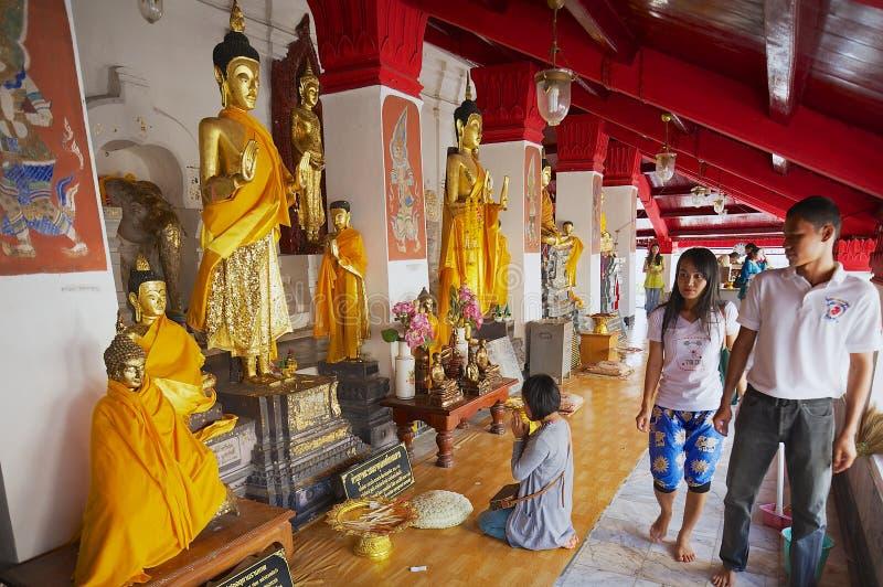 La gente visita el oro cubrió las estatuas de Buda en el templo de Wat Phra Mahathat Woramahawihan en Nakhon Sri Thammarat, Taila foto de archivo libre de regalías