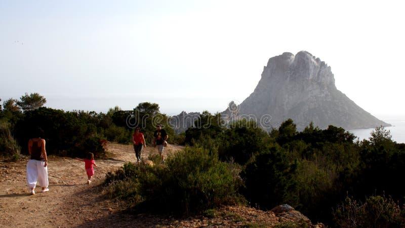La gente waliking a lo largo del parque natural llamó Es Vedrat y la montaña grande famosa en el fondo fotos de archivo