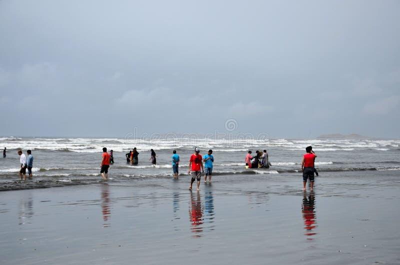 La gente y las familias vadean en agua y gozan de las ondas en la playa Karachi Paquistán de la opinión del mar imagenes de archivo
