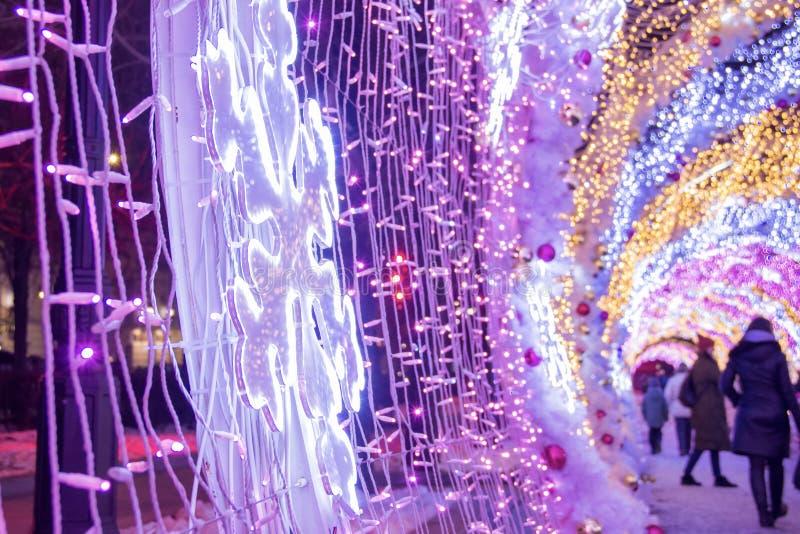 La gente y los turistas caminan a lo largo de la calle de Tverskaya adornada por días de fiesta del Año Nuevo y de la Navidad Luz imagen de archivo