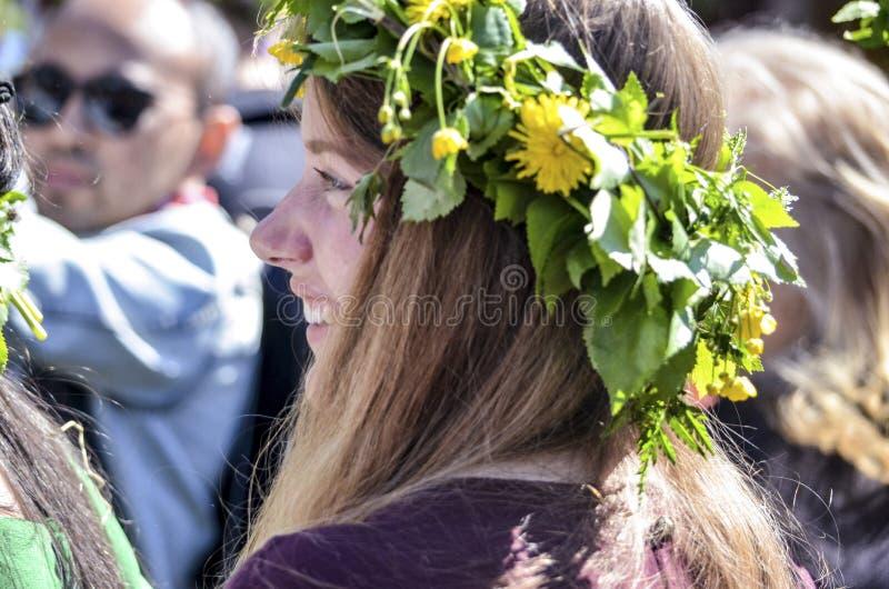 La gente y la mujer suecas hermosas est?n gozando de la mediados de corona que lleva del d?a de verano hicieron de hojas en d?a s fotos de archivo libres de regalías