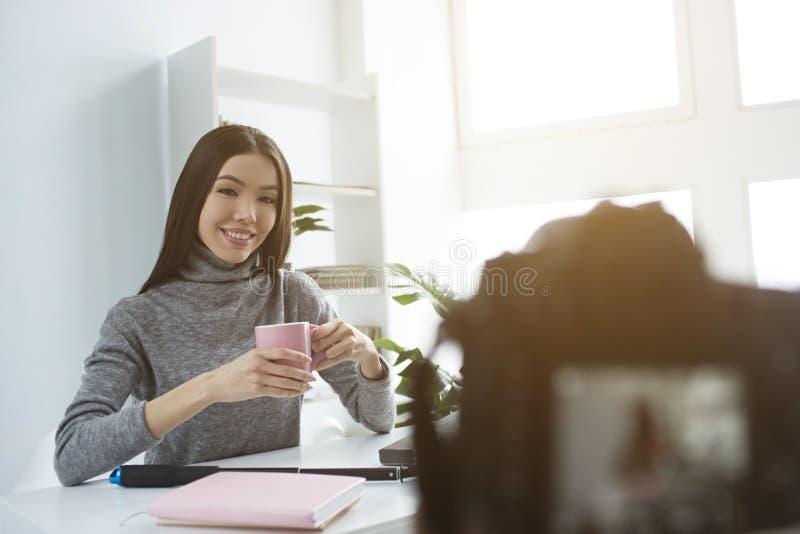 La gentille et attirante fille est sittingat la table et le thé potable de la tasse rose Elle fait cela devant l'appareil-photo photo stock