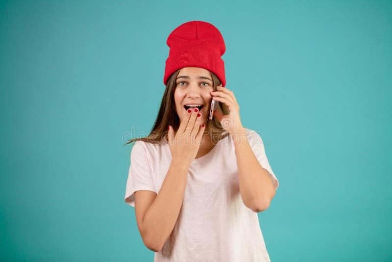 La gentille femme dans l'équipement occasionnel et le chapeau rouge baîlle tout en parlant au téléphone photos libres de droits