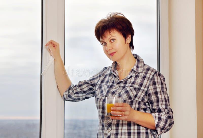 La gentille femme se tient prêt la fenêtre avec le verre de jus image stock