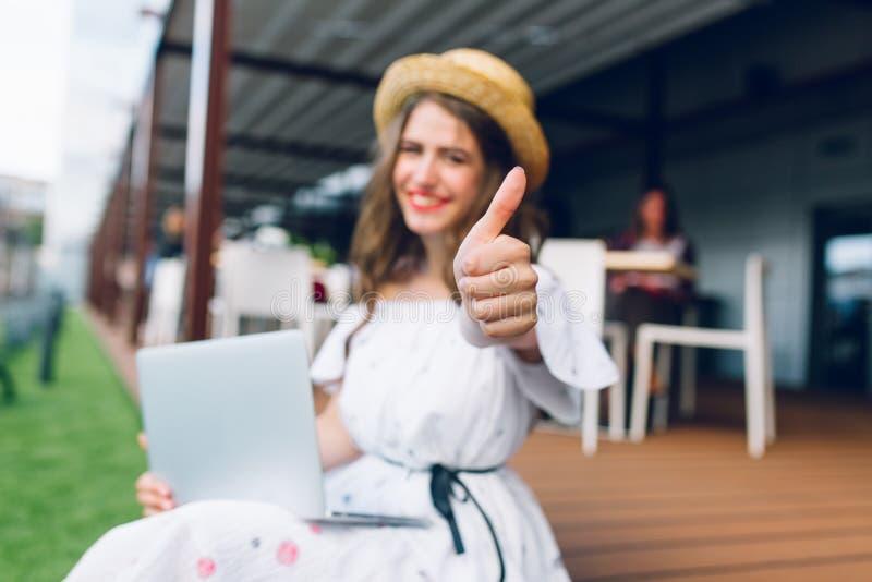 La gentille fille avec de longs cheveux dans le chapeau s'assied sur le plancher sur la terrasse Elle porte une robe blanche avec photographie stock
